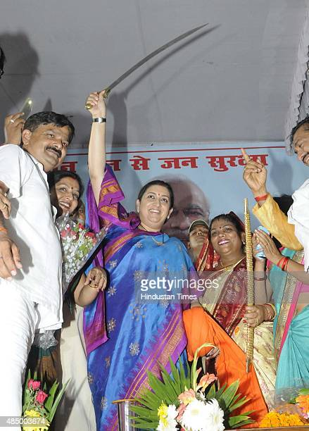 Union Minister Smriti Irani presented with a sword soon after her arrival during a rally where she paid premiums for PM's Suraksha Bima Yojana for...