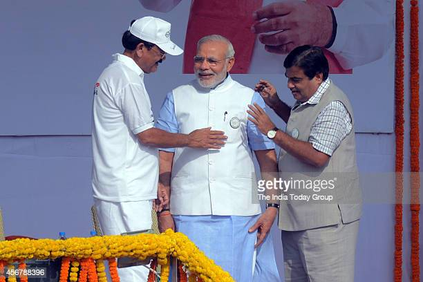 Union ministers Nitin Gadkari and M Venkaiah pinning a badge on Prime Minister Narendra Modi's jacket during the launch of nationwide cleanliness...