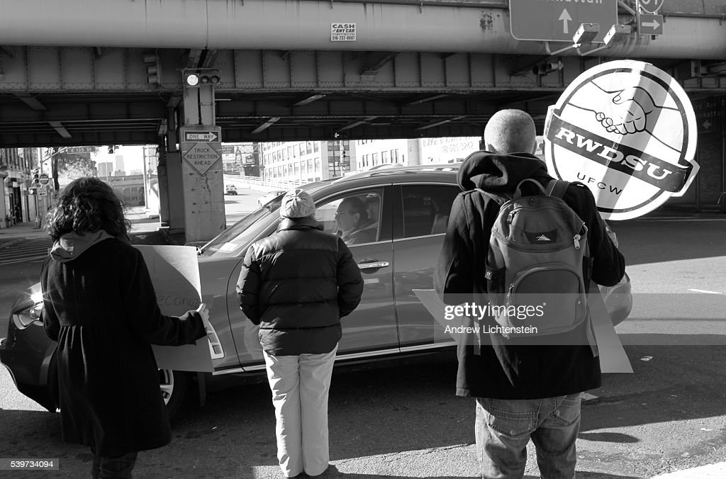 Union organizers watch as a driver crosses a picket line Car wash workers go on strike and form a picket line to discourage drivers to use Sunny Day...