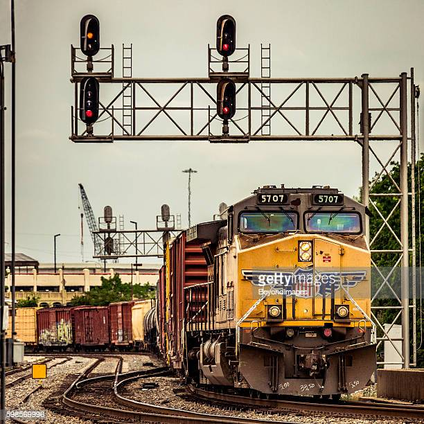 Union Pacific (UP) freight train passing under city signal gantry