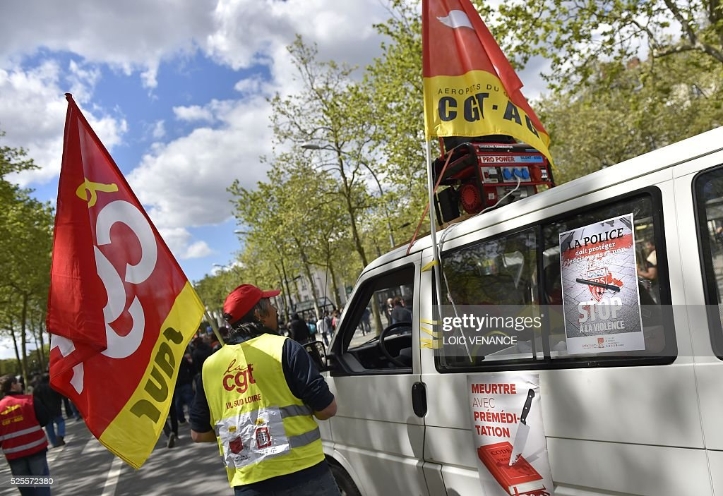 A CGT union poster (R) reading 'Police should protect citizens and not beat them, stop violence' is pictured during a demonstration against the French government's proposed labour reforms on April 28, 2016 in Nantes. Protests turned violent in Paris and other French cities today as tens of thousands of workers and students made a new push for the withdrawal of a hotly contested labour bill. / AFP / LOIC