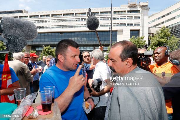 A union representative of ailing car parts factory GmS Industry speaks with head of the CGT union Philippe Martinez during a rally in front of the...