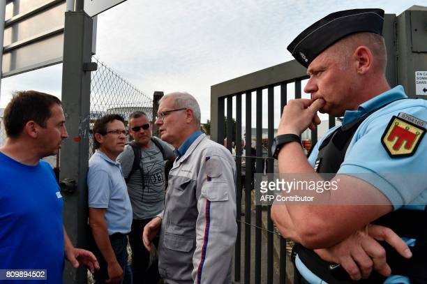 A union representative talks with director of the SeptFons foundry Jean Sevagen as a Gendarme looks on as unionists announced the end of a blockade...