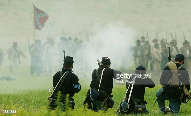 Union soldiers fire at Confederate soldiers during a Civil War reenactment battle August 9 2003 in Gettysburg Pennsylvania Civil War reenactors from...