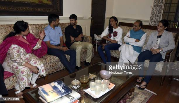 Union Sports Minister Vijay Goel with his wife Preeti Goel talking to Badminton players Saina Nehwal PV Sindhu Srikanth Kidambi and their coaches P...