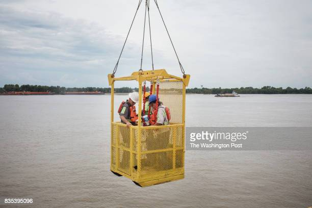 Union workers are carried down into the barge to continue loading of coils of steel at The Port of New Orleans in New Orleans Louisiana on June 27...