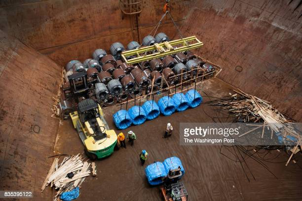 Union workers work to load coils of steel into a barge at The Port of New Orleans in New Orleans Louisiana on June 27 2017