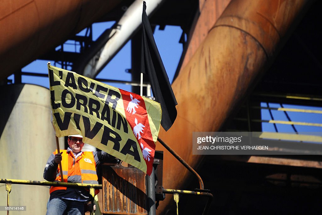 A CFDT unionist of steel giant ArcelorMittal's blast furnaces of Florange, eastern France, carries a black flag to install on the blast furnace, on April 25, 2013 in Hayange. The ArcelorMittal-owned Florange plant, in the heart of the northeastern Lorraine region, has become a symbol for the dismantlement of France's industrial sector, from which 750,000 jobs have disappeared over the past decade. VERHAEGEN