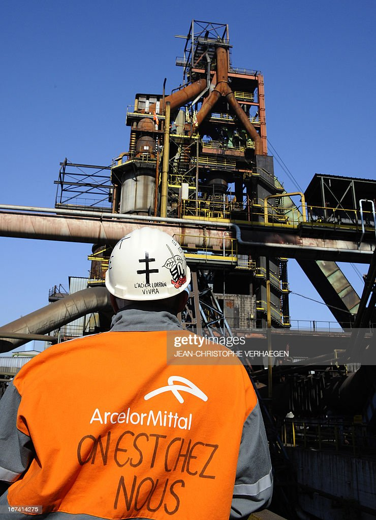 CFDT unionist of steel giant ArcelorMittal's blast furnaces of Florange, eastern France, looks at his colleagues who install a black flag on the blast furnace, on April 25, 2013 in Hayange. The ArcelorMittal-owned Florange plant, in the heart of the northeastern Lorraine region, has become a symbol for the dismantlement of France's industrial sector, from which 750,000 jobs have disappeared over the past decade. VERHAEGEN
