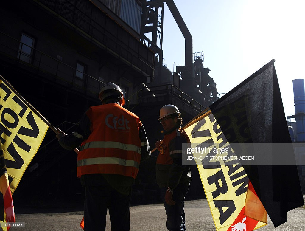 CFDT unionists and employees of steel giant ArcelorMittal's blast furnaces of Florange, eastern France, carry a black flag to install on the blast furnace, on April 25, 2013 in Hayange. The ArcelorMittal-owned Florange plant, in the heart of the northeastern Lorraine region, has become a symbol for the dismantlement of France's industrial sector, from which 750,000 jobs have disappeared over the past decade. VERHAEGEN
