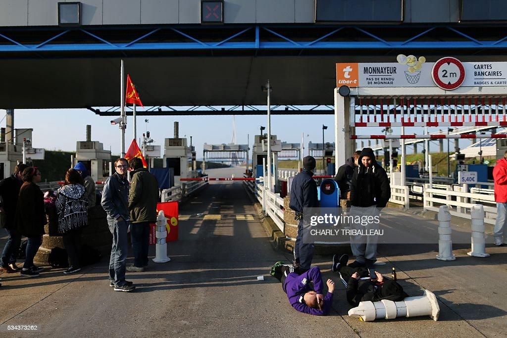 Unionists block the tollgate of the 'Pont de Normandie', in Le Havre northwestern France, on May 26, 2016, to protest against the government's proposed lab our reforms. Refinery workers stepped up strikes that threaten to paralyse France weeks ahead of the Euro 2016 tournament as the government moved to break their blockades, escalating a three-month tug-of-war over labour reforms. / AFP / CHARLY