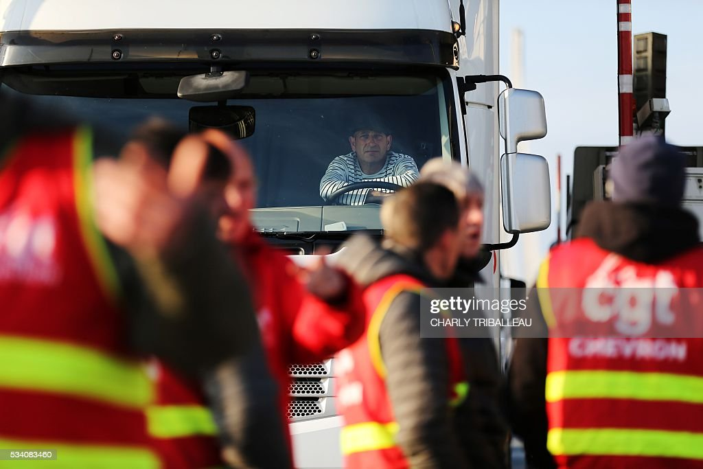 Unionists block the trucks' tollgate of the 'Pont de Normandie', in Le Havre northwestern France, on May 25, 2016, to protest against the government's proposed labour reforms. Refinery workers stepped up strikes that threaten to paralyse France weeks ahead of the Euro 2016 tournament as the government moved to break their blockades, escalating a three-month tug-of-war over labour reforms. / AFP / CHARLY