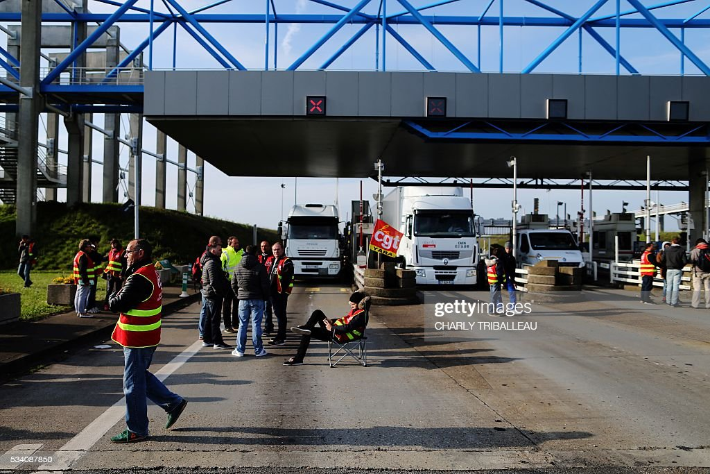 Unionists block the trucks' tollgate of the 'Pont de Normandie', in Le Havre northwestern France, on May 25, 2016, to protest against the government's proposed labour reforms. Refinery workers stepped up strikes that threaten to paralyse France weeks ahead of the Euro 2016 tournament as the government moved to break their blockades, escalating a three-month tug-of-war over labour reforms. / AFP PHOTO / CHARLY TRIBALLEAU Refinery workers stepped up strikes that threaten to paralyse France weeks ahead of the Euro 2016 tournament as the government moved to break their blockades, escalating a three-month tug-of-war over labour reforms. / AFP / CHARLY