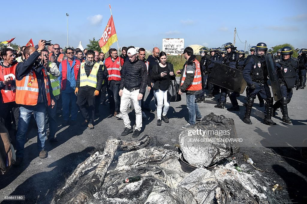 Unionists workers on strike block the access to an oil depot near the Total refinery of Donges, western France, to protest against the government's planned labour law reforms, on May 27, 2016. The French government's labour market proposals, which are designed to make it easier for companies to hire and fire, have sparked a series of nationwide protests and strikes over the past three months. French unions on May 27 called on workers to 'continue and step up their action', as a wave of strikes against a disputed labour law disrupted transport and fuel supplies. / AFP / JEAN