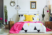Unique white bedroom with colorful pillows, geometric bedclothes and cactus