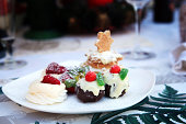 A different take on the classic Christmas pudding, with meringue and cream, icing and berries to top it off. A shortbread star is shown out of focus in the background.