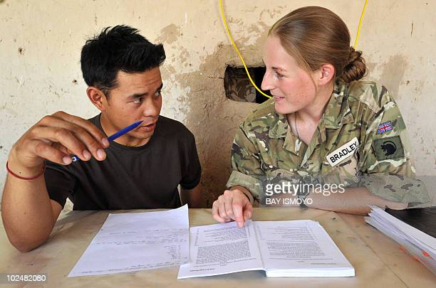 Unit Education Officer of 1st Battalion the Royal Gurkha Rifles Captain Abi Bradley tutors Corporal Bhim Gurung for a literacy and numeracy exam at a...