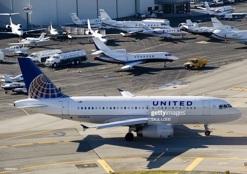 A United Airlines Airbus A319 airplane waits on a taxiway to takeoff alongside private jets at John Wayne Airport in Santa Ana, California, February 16, 2012. When United and Continental complete their merger, the combined airline will operate over 5,600 flights to 376 airports on six continents. AFP PHOTO / Saul LOEB