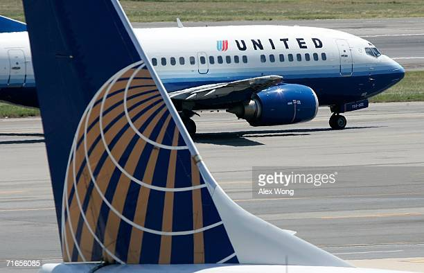 United Airlines aircraft passes by a Continental Airlines aircraft as it taxis to takeoff from the runway of Ronald Reagan National Airport August 16...