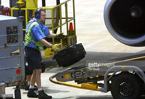 United Airlines baggage handler loads a plane at the Chicago O''Hare International Airport June 18 2001 in Chicago Illinois United Airlines resumed...