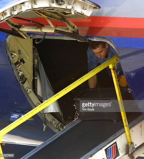 United Airlines baggage handler unloads a plane at O''Hare International Airport June 18 2001 in Chicago Illinois United Airlines resumed...