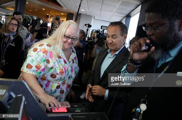 United Airlines CEO Oscar Munoz looks on as a passenger scans her boarding pass for United Airlines flight 747 on its final flight from San Francisco...