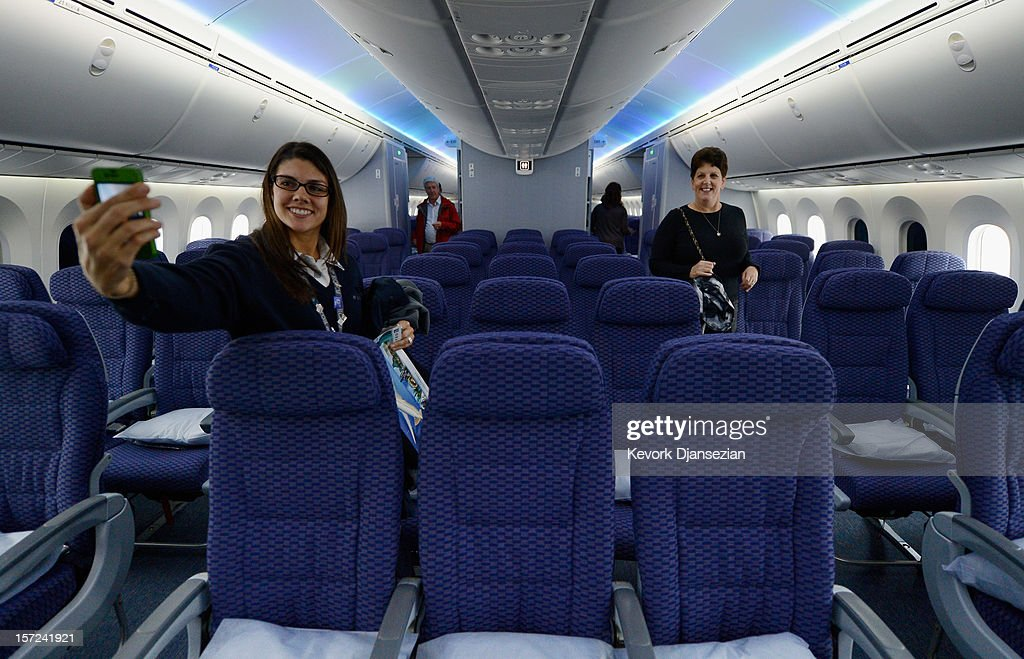 United Airlines customer service representative Desiree Yoos (L) takes a her picture inside the cabin while touring the new Boeing 787 Dreamliner at Los Angeles International Airport on November 30, 2012 in Los Angeles, California. In January the new jet is scheduled to begin flying daily non-stop between Los Angeles International airport and Japan's Narita International Airport and later to Shanghai staring in March. The new Boeing 787 Dreamliner will accommodate 219 travelers with 36 seats in United Business First, 70 seats in Economy Plus and 113 in Economy Class. The carbon-fiber composite material that makes up more than 50 percent of the 787 makes the plane more fuel-efficient.