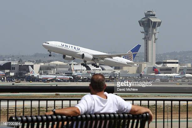 United Airlines jet passes the air traffic control tower at Los Angles International Airport during takeoff on April 22 2013 in Los Angeles...