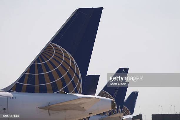 United Airlines jets sit at gates at O'Hare International Airport on September 19 2014 in Chicago Illinois In 2013 67 million passengers passed...