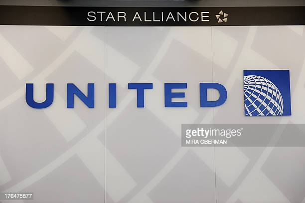 A United Airlines logo is seen behind the ticket counter at Chicago's O'Hare airport on August 13 2013 The US Justice Department and several states...