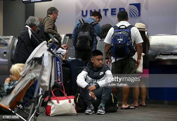 United Airlines passengers wait in line to check in for flights at San Francisco International Airport on July 8 2015 in San Francisco California...