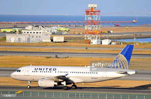 A United Airlines plane taxis on the runway while a crashed Asiana Airlines Boeing 777 is seen on the runway at San Francisco International Airport...