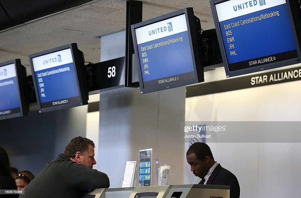 A United Airlines ticket agent helps a customer rebook a flight that was canceled due to weather at San Francisco International Airport on February 8, 2013 in San Francisco, California. Thousands of flights to the East Coast were canceled as a potentially historic blizzard is set to dump up to three feet of snow in the Northeast from New York City to Boston.
