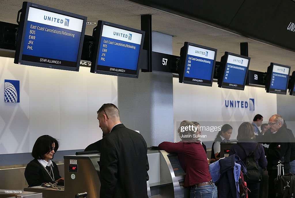 United Airlines ticket agents help customers rebook flights that were canceled due to weather at San Francisco International Airport on February 8, 2013 in San Francisco, California. Thousands of flights to the East Coast were canceled as a potentially historic blizzard is set to dump up to three feet of snow in the Northeast from New York City to Boston.