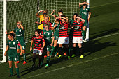 United and Wanderers players shield their eyes from the sun as they wait for a corner to restart play during the round one WLeague match between the...