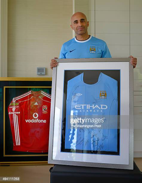 United Arab Emirates ambassador Yousef Al Otaiba is shown wearing a Manchester City shirt and holding a framed shirt from 2 years ago of the...