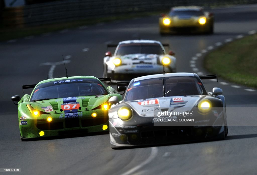 United Arab Emirates driver Khaled al-Qubaisi (R) in Porsche 911 RSR N°88 and British driver Ben Collins (L) in his Ferrari 458 Italia N°57 compete during the 82nd Le Mans 24 hours endurance race, on June 15, 2014 in Le Mans, western France. Fifty-six cars with 168 drivers are participating on June 14 and 15 in the Le Mans 24-hours endurance race.