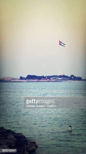 United Arab Emirates Flag By Sea Against Clear Sky