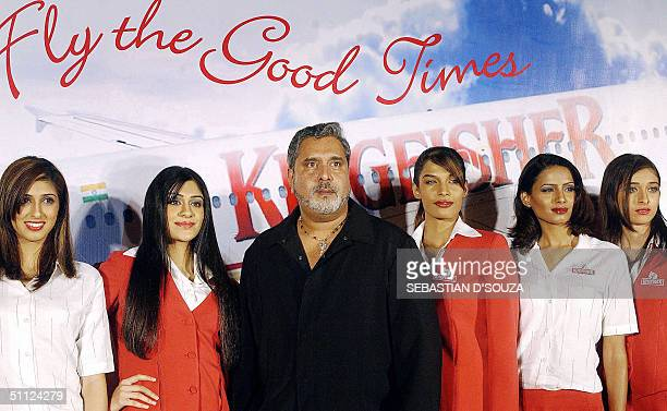 United Breweries group chairman Vijay Mallya poses along with flight attendants late 28 July 2004 in Bombay during a ceremony organised ahead of the...