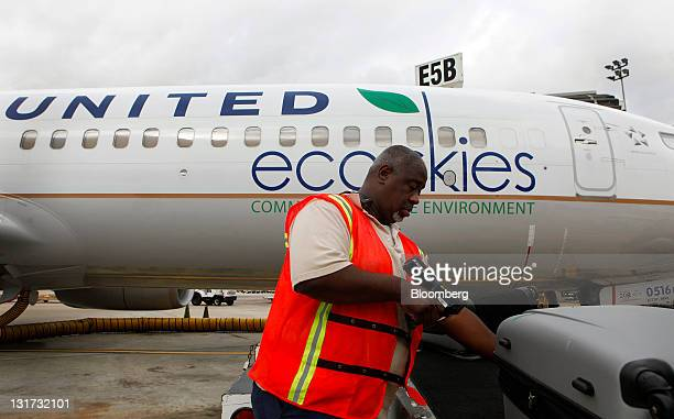 A United Continental Holdings Inc employee loads a bag onto a Boeing 737800 bearing the Eco Skies livery at George Bush Intercontinental Airport in...
