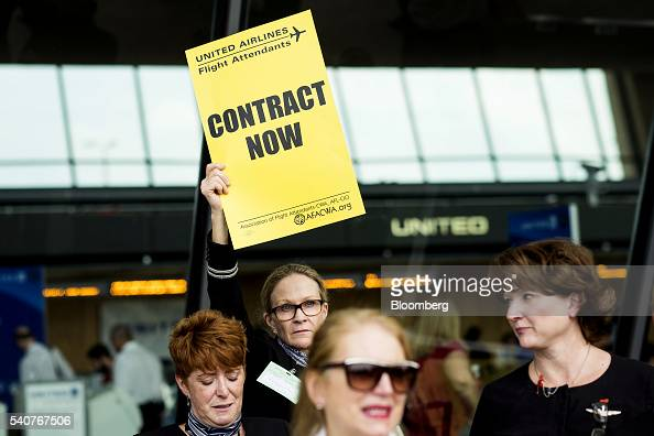 A United Continental Holdings Inc flight attendant holds a sign while picketing for a new contract at Dulles International Airport in Dulles Virginia...