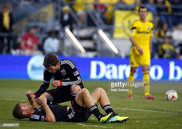 C United defender Bobby Boswell helps defender Jeff Parke off the ground during the first half of their game at Columbus Crew Stadium on April 19...
