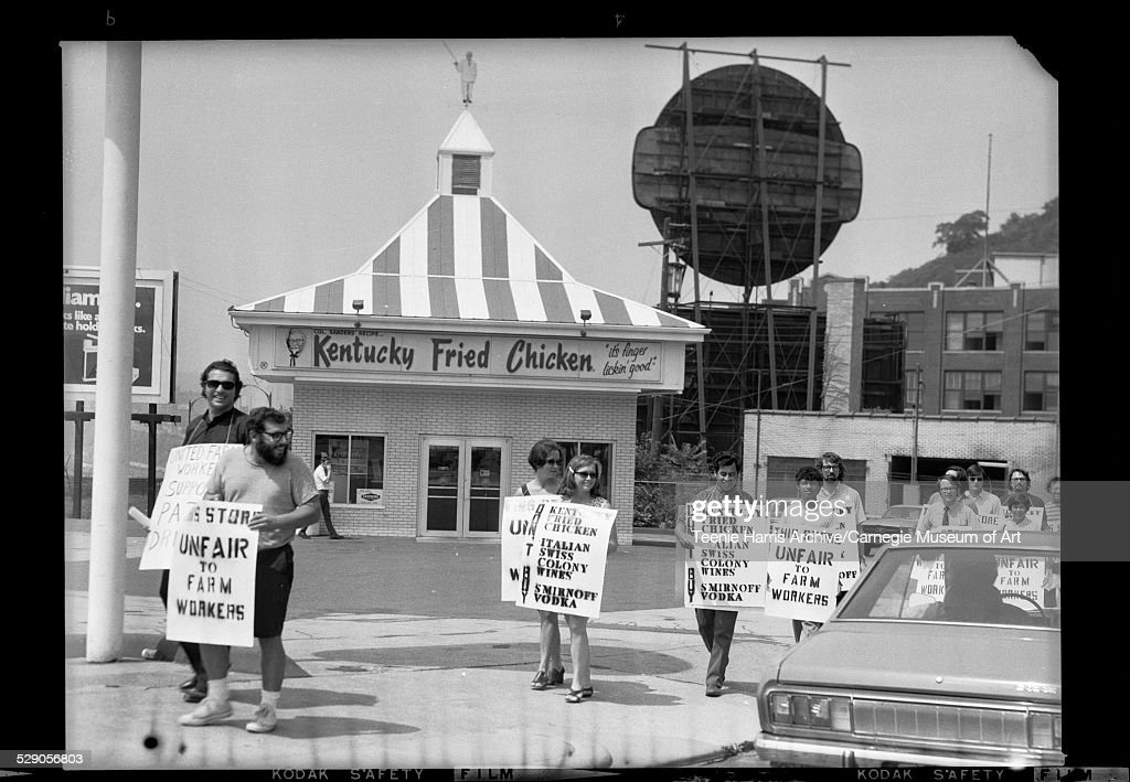 United Farm Workers protesters with sandwich boards reading 'This Store Unfair to Farm Workers' outside Kentucky Fried Chicken on the Boulevard of...