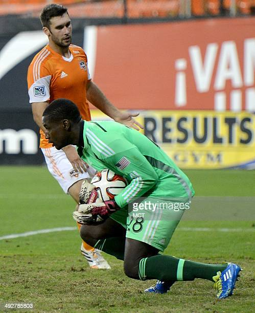 DC United goalkeeper Bill Hamid covers the ball before Houston Dynamo forward Will Bruin left can make a play on it in the second half at RFK Stadium...