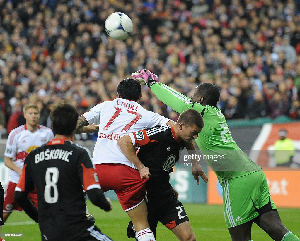 D.C. United goalkeeper Bill Hamid (28) punches a New York Red Bulls pass out of the goal area as D.C. United midfielder Perry Kitchen (23) battles New York Red Bulls midfielder Tim Cahill (17) during first-half action in an MLS Eastern Conference semifinal at RFK Stadium in Washington, D.C., Saturday, November 3, 2012.
