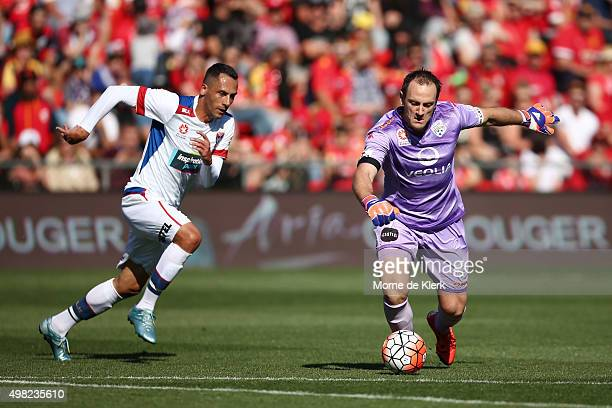 United goalkeeper Eugene Galekovic clears the ball in front of Milos Trifunovic of Newcastle Jets during the round seven ALeague match between...