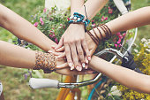 United hands of young females. Stylish hands of girlfriends in boho hippie bracelets near bicycle handlebar, top view. Togetherness and support, youth fashion and active lesiure. Women friendship