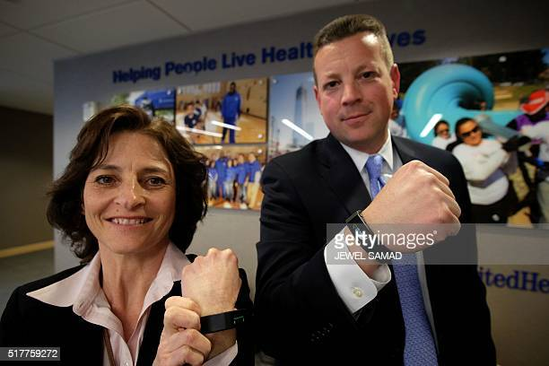 United Healthcare executives Jean McGann and Chuck Cerniglia pose wearing special activity trackers at their office in New York on March 24 2016...
