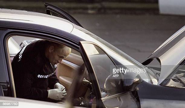 A forensics expert examines a car in an industrial estate in Welling in southeast London 03 March 2006 following a raid where police investigating...