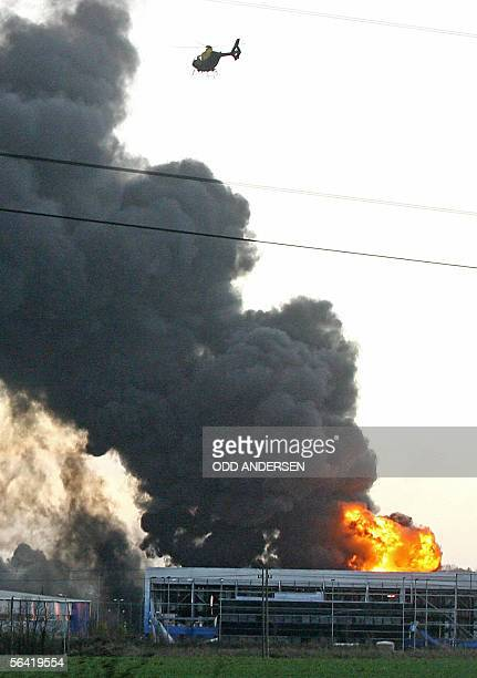 A helicopter overflies a fierce fire at the center of an explosion at Buncefield oil depot in Hemel Hempstead on the outskirts of London 12 December...